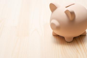 木目の背景に豚の貯金箱