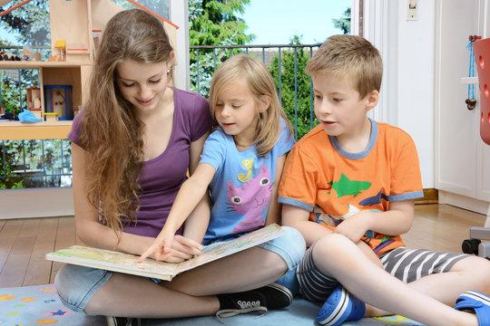 Babysitter schaut Buch mit Kindern