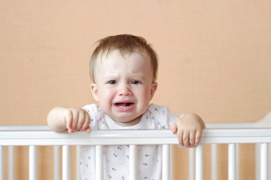crying baby age of 11 months in white bed