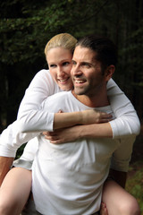Man is happily carrying his wife on his back