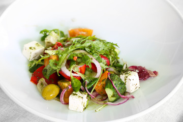Greek salad on white plate, close up