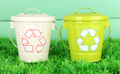 Recycling bins on green grass on color wooden background