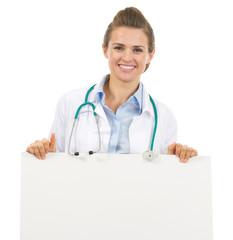 Smiling doctor woman showing blank billboard