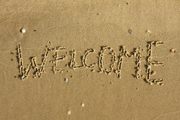 Word welcome written on the sand