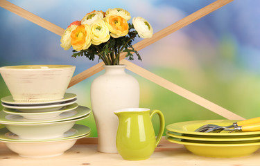 Beautiful dishes on wooden cabinet on natural background