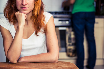 Woman is thinking while her boyfriend is cooking