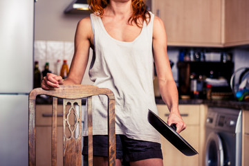 Young woman with frying pan in kitchen
