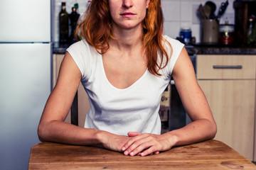 Calm woman sitting in her kitchen