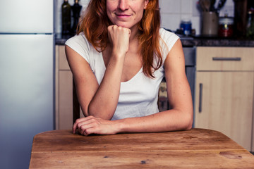Happy woman relaxing in her kitchen