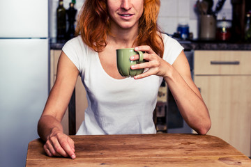 Woman drinking from cup in her kitchen