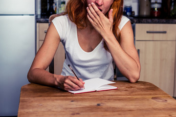 Tired woman writing in her kitchen