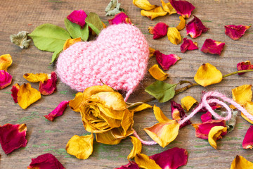 cute pink knitted heart on a wooden background