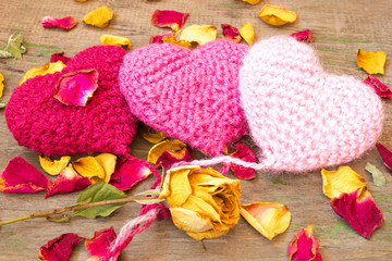 three knitted hearts on a wooden background
