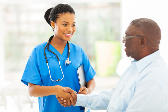 african american medical nurse handshaking with senior patient