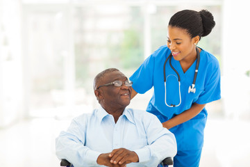 african nurse taking care of senior patient in wheelchair