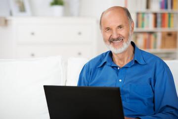 lächelnder senior mit laptop zu hause