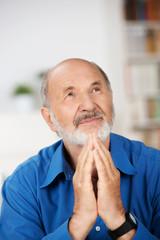 älterer mann mit gefalteten händen