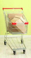 Shopping cart with carton, on green wall background