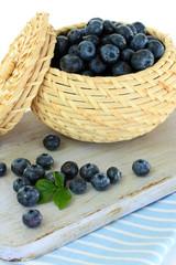 Blueberries in wooden basket on board on napkin