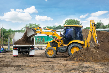 Tractor with front and loader bucket and backhoe with truck