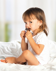 little girl eating chocolate candy in bed
