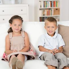 zwei süße kinder sitzen auf dem sofa