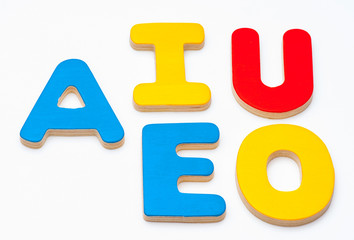 AEIOU, the first five letters of the alphabet colored wood