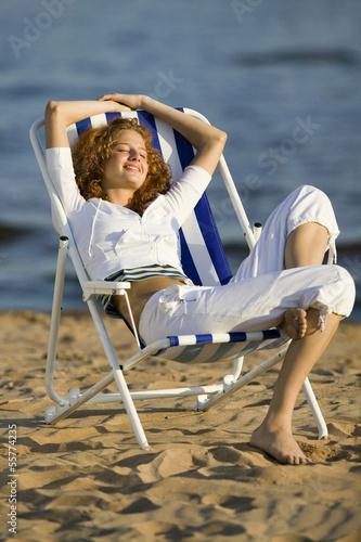 junge frau sitzt im liegestuhl am strand die augen geschlossen stockfotos und lizenzfreie. Black Bedroom Furniture Sets. Home Design Ideas