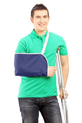 Smiling male with broken arm and crutch