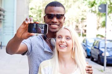 junges lachendes multkulturelles paar machen foto mit smartphone