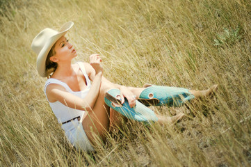 Young woman in cowboy hat and boots sitting in the yellow grass,