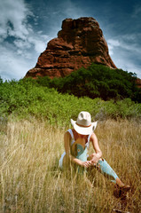 Woman in cowboy hat and boots in the mountains