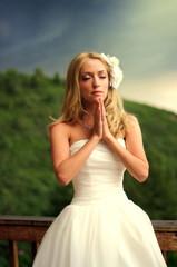 Young beautiful bride praying