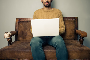 Young man with laptop on old sofa