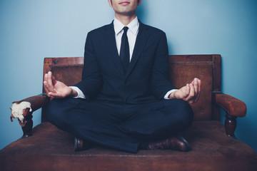 Businessman is meditating on sofa
