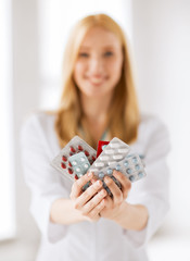 female doctor with packs of pills