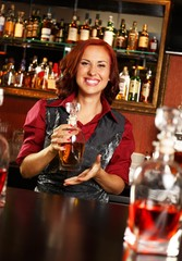 Beautiful barmaid with bottle behind bar counter