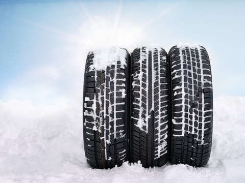 Three snowy winter tyres in front of blue sky with sunlights