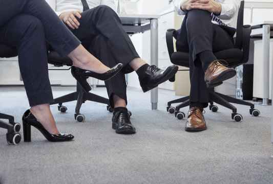 Three business people with legs crossed sitting on chairs, low section