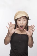 Portrait of surprised woman with hands raised, studio shot