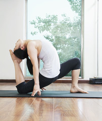 Woman bent over backwards in a yoga position in a yoga studio, side view