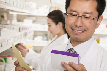 Pharmacist looking down and examining prescription medication in a pharmacy