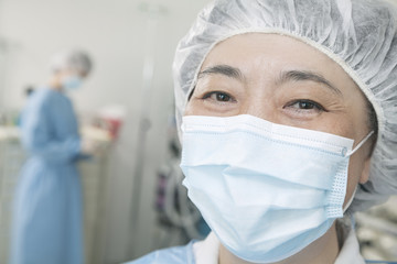 Portrait of surgeon with surgical mask and surgical cap in the operating room