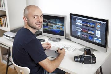 Jeune homme photographe retouchant ses photos sur son ordinateur