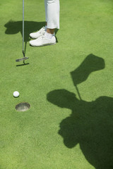Low section of young woman hitting the ball on the golf course, focus on the hole
