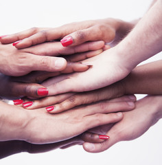 Close-up on a pile of hands on top of each other, multi-ethnic group of people, studio shot