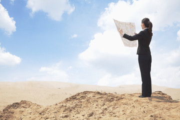 Young Businesswoman looking at a map in the middle of the desert
