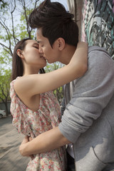 Happy young couple with arms around each other kissing by a wall with graffiti