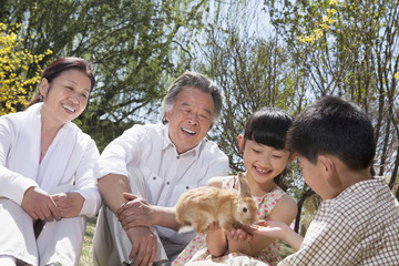 Grandparents with their grandchildren and their pet rabbit sitting in the park in springtime