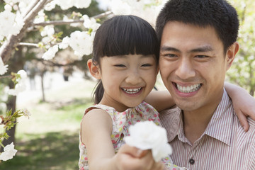 Smiling father and daughter enjoying the cherry blossoms on the tree in the park in springtime, daughter holding a flower